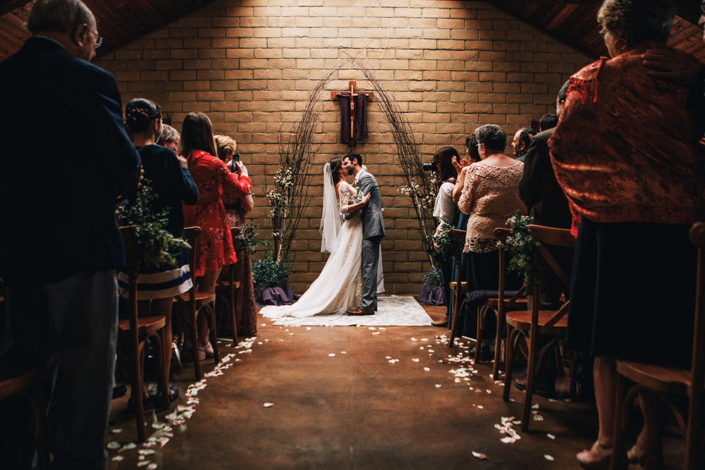 san diego wedding   photographer | bride and groom kissing down the aisle with crowd standind up   applauding