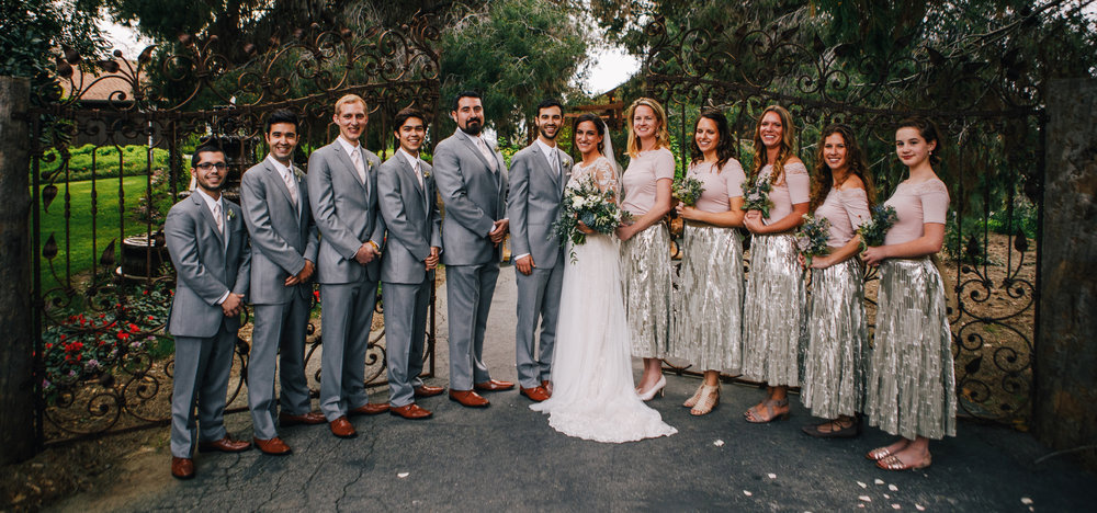 san diego wedding   photographer | men in grey suits and women in dresses lined up in front of   ajar gate