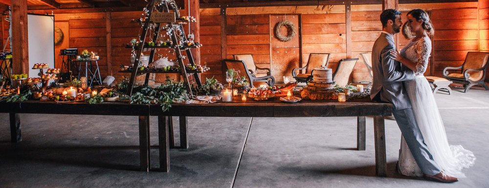 san diego wedding   photographer | long shot of groom leaning against table with food and bride   leaning against groom
