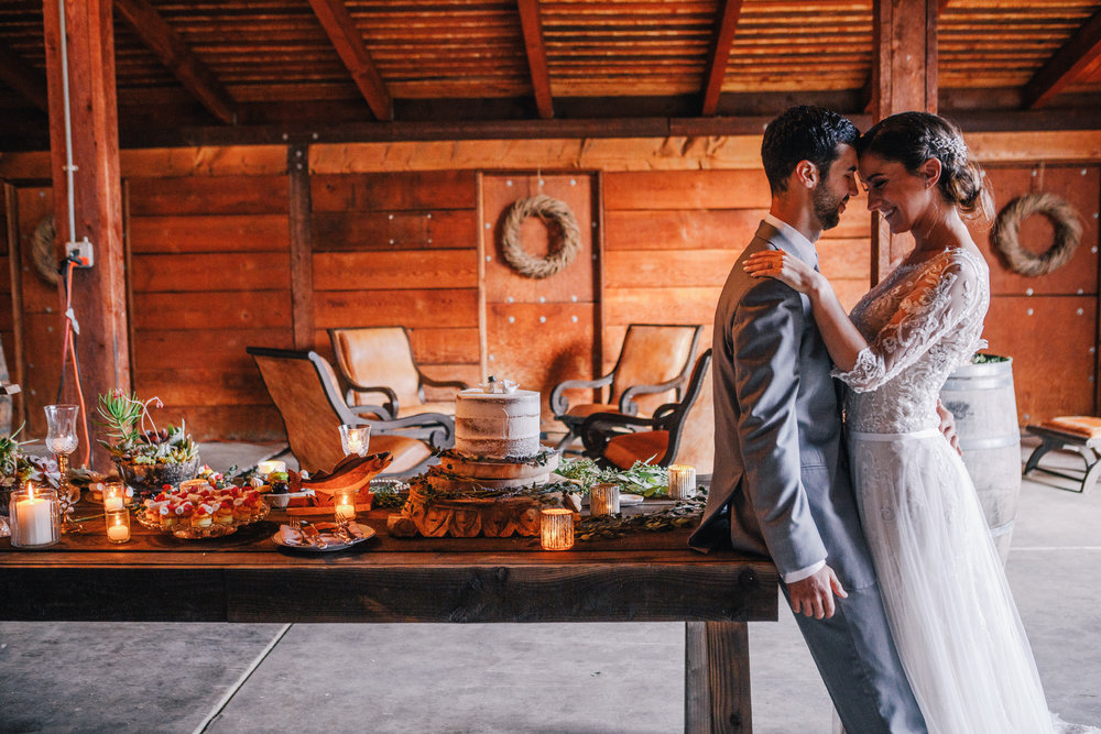 san diego wedding   photographer | groom leaning against table with food on it and bride leaning   against groom