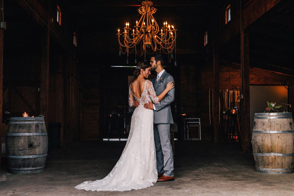 san diego wedding   photographer | bride and groom dancing inside barn under chandelier with   barrels at their side