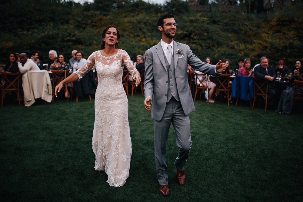 san diego wedding   photographer | bride and groom walking with arms out wide open with crowd   behind them