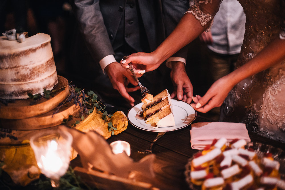san diego wedding   photographer | arms of bride and groom about to take a piece of cake