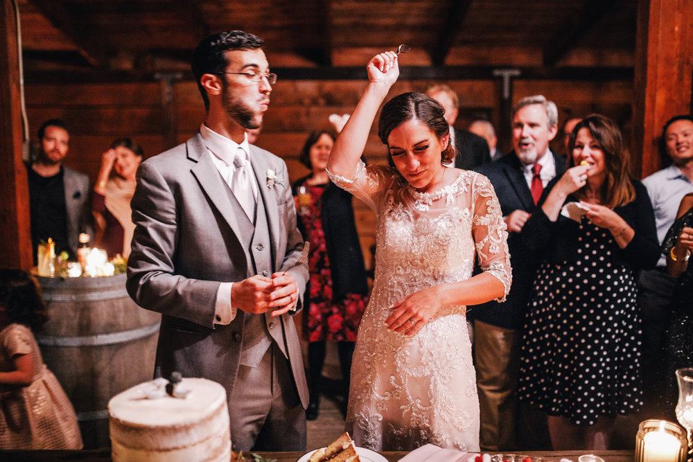 san diego wedding   photographer | groom eating a piece of cake while bride's hand is up