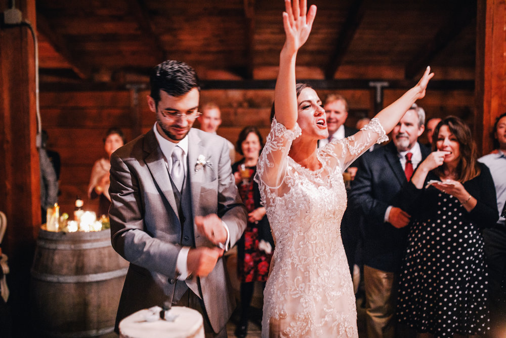 san diego wedding   photographer | bride with her arms up high facing crowd while groom fixes   sleeve