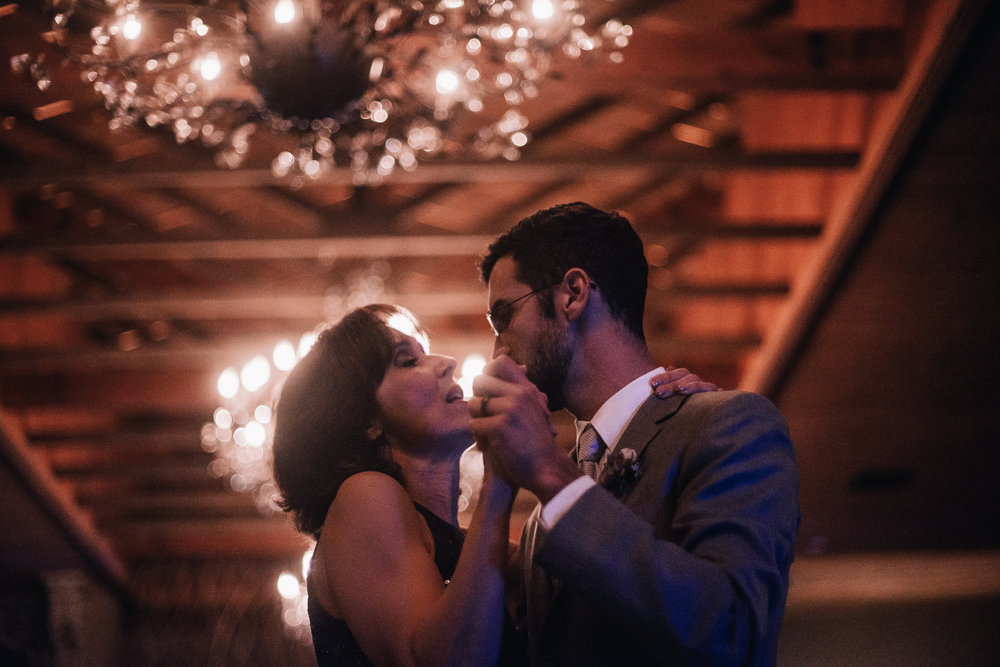 san diego wedding   photographer | groom dancing with woman wearing black dress under the light   of a chandelier