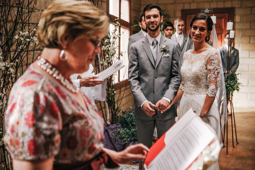 san diego wedding   photographer | bride and groom standing side by side holding each other's   hands while looking at woman reading from a piece of paper