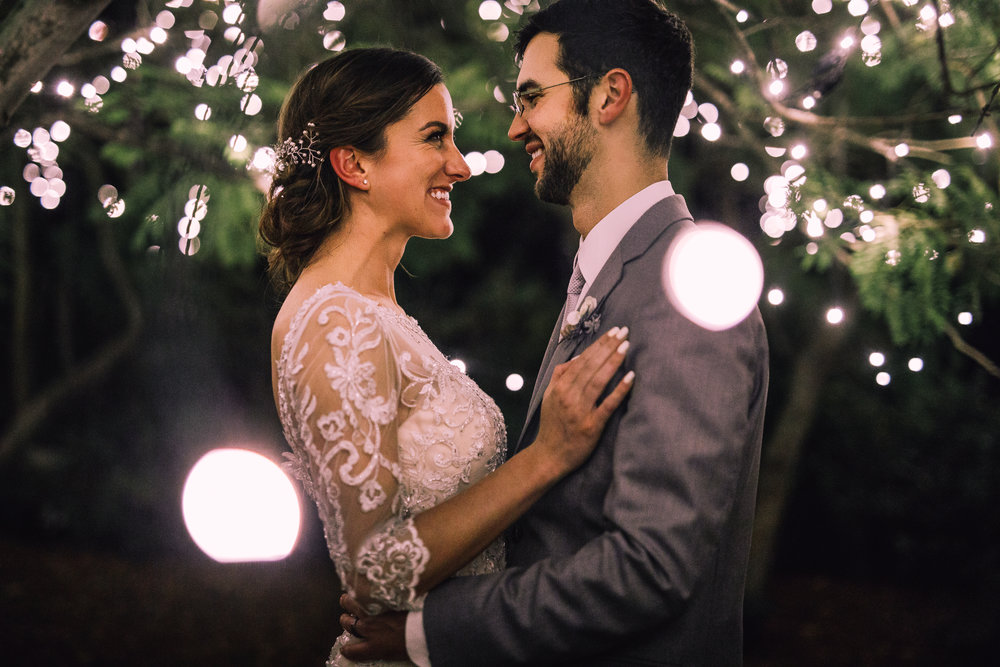 san diego wedding   photographer | bride standing close to groom with her hand on groom's   chest under lights