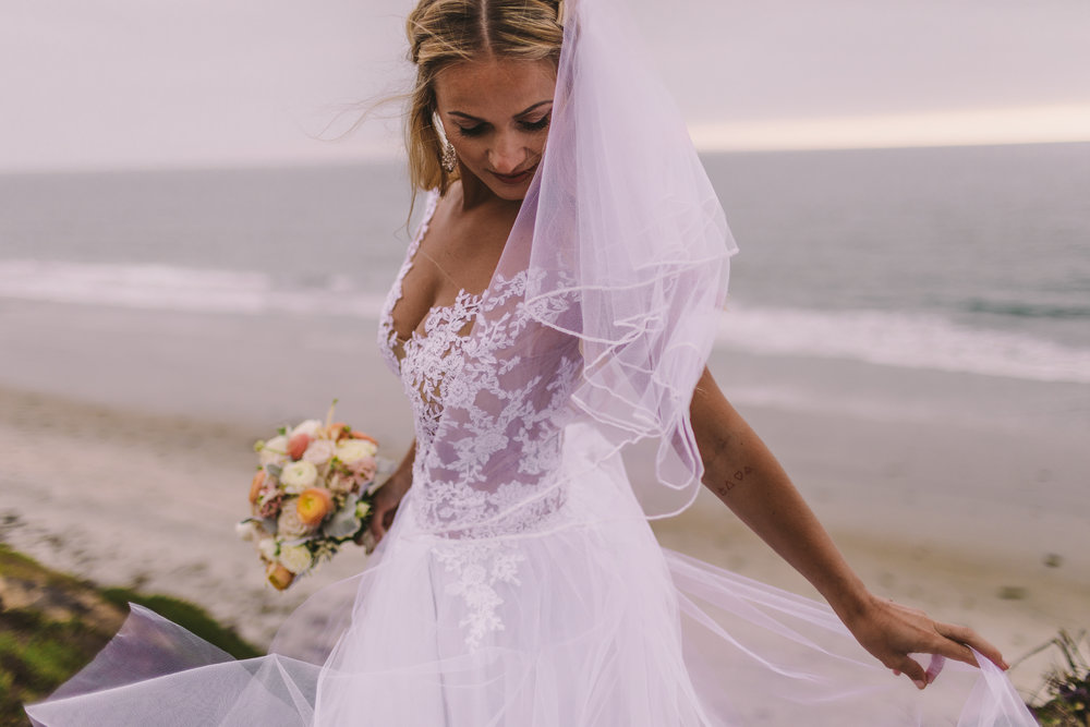 san diego wedding   photographer | woman in white dress holding bouquet of flowers looking down   to her side on a beach