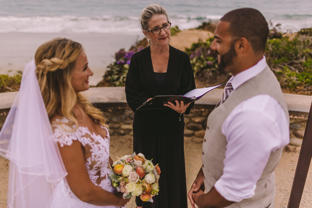 san diego wedding   photographer | picture of bride and groom standing in front of officiator   smiling at each other