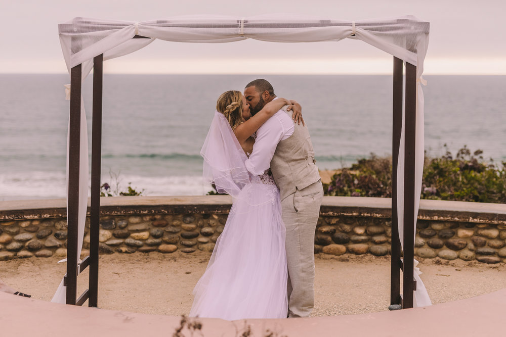 san diego wedding   photographer | married couple kissing each other under cloth help up by   wooden structure