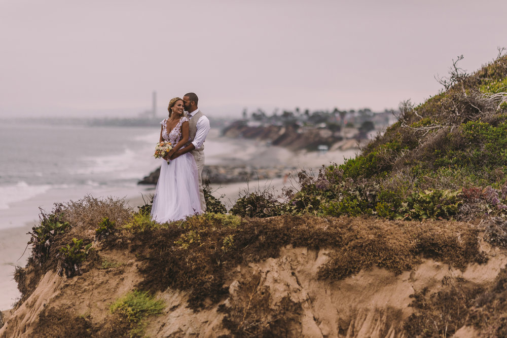 san diego wedding   photographer | man holding woman from behind with woman holding bouquet of   flowers on sea cliff