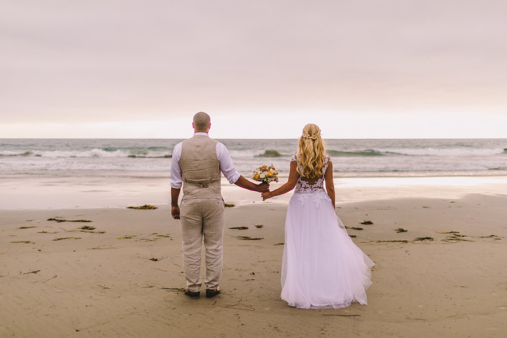 san diego wedding   photographer | married couple holding a bouquet of flowers between them while   looking at the sea