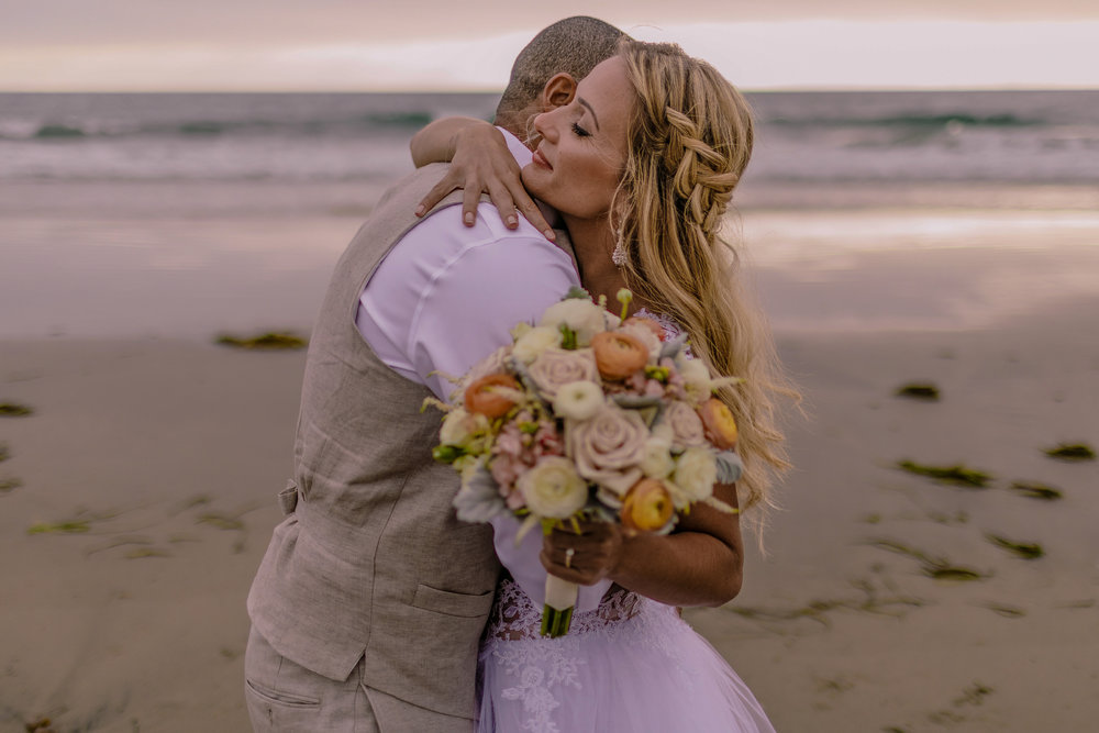 san diego wedding   photographer | man hugging woman with woman holding bouquet of flowers in   front of camera