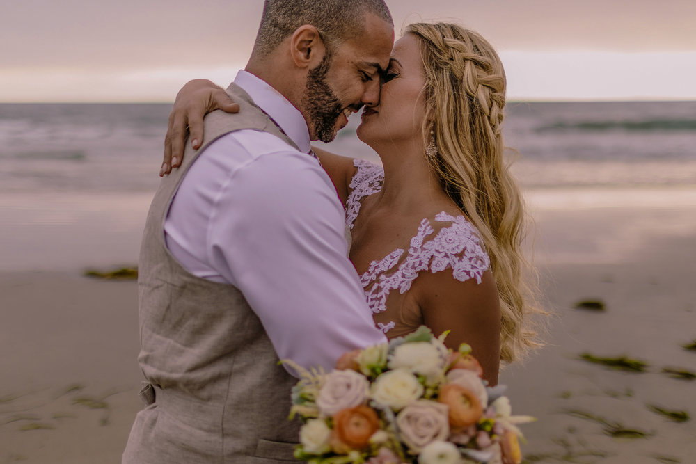 san diego wedding   photographer | married couple about to kiss with woman's arm around man's   back with woman holding bouquet of flowers in front of camera