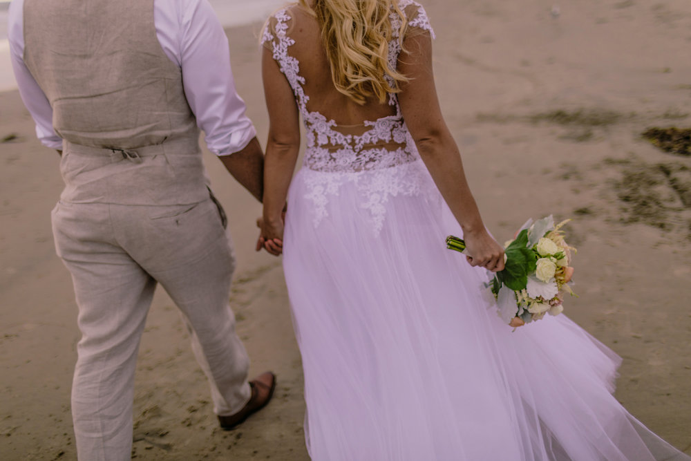 san diego wedding   photographer | married couple holding hands walking away from the camera with   woman holding bouquet of flowers