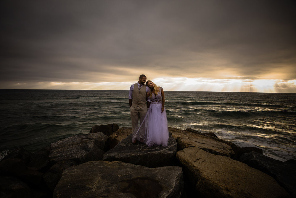 san diego wedding   photographer | bride leaning her head against groom's shoulder with sunrays   visible from afar