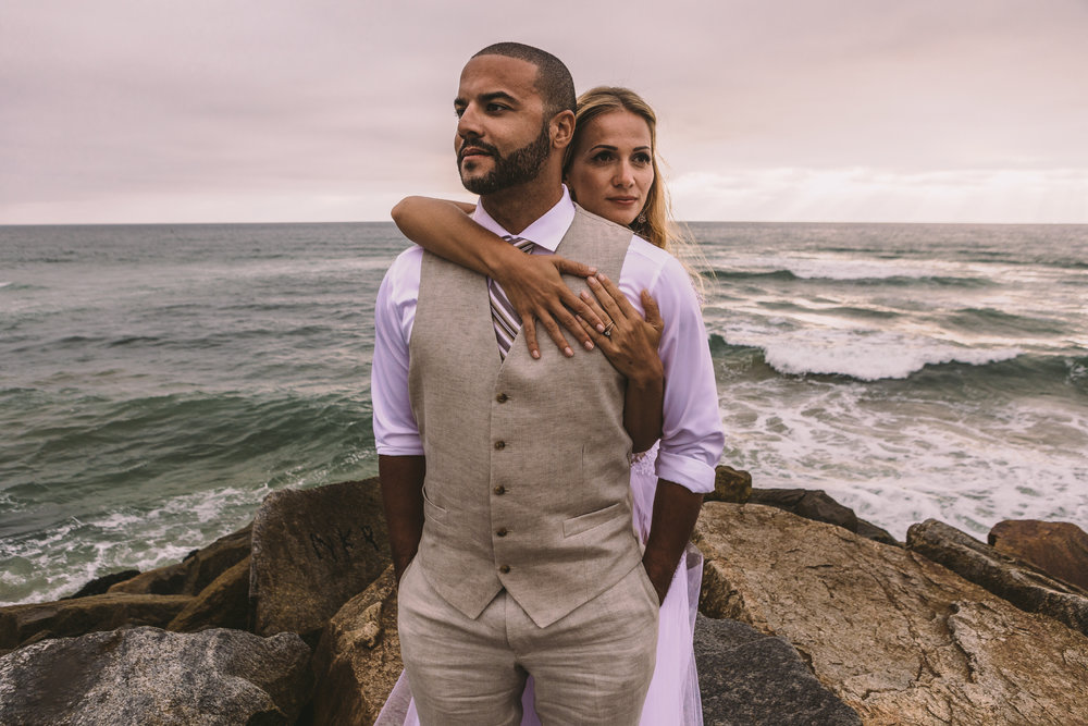 san diego wedding   photographer | bride hugging groom from behind on top of rocky shore with the   sea seen behind them