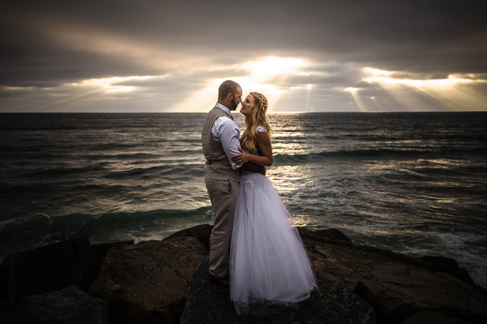 san diego wedding   photographer | married couple about to kiss each other with sunrays visible   from afar