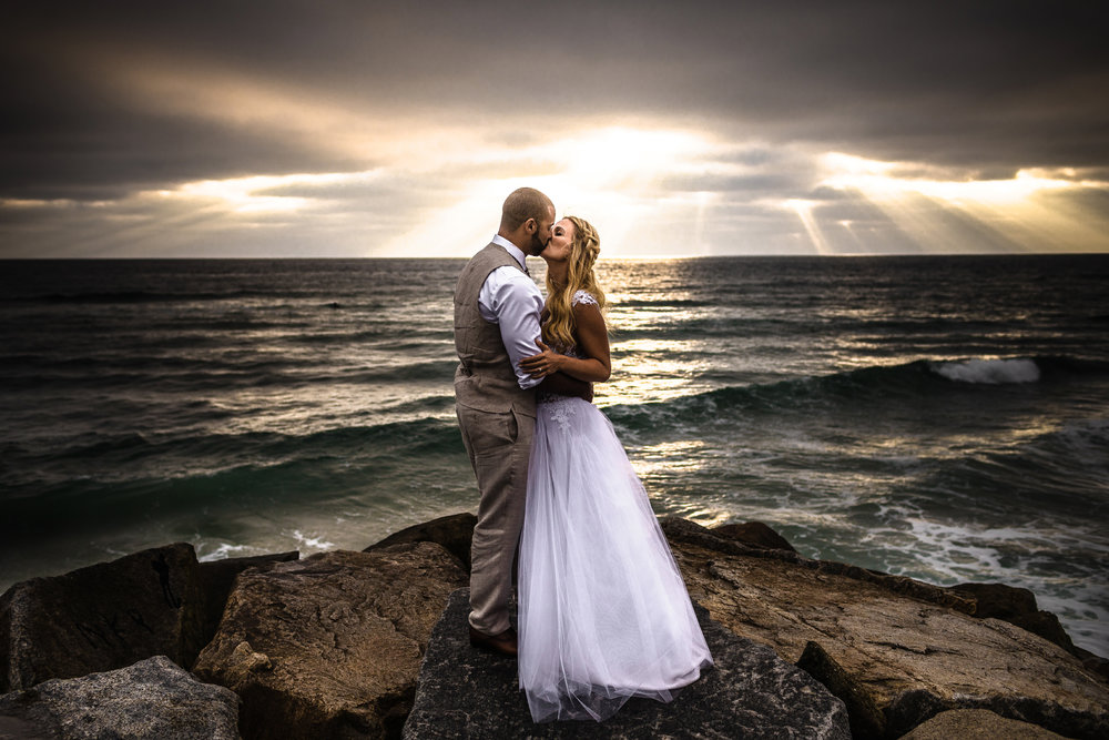 san diego wedding   photographer | married couple kissing with woman's arm holding man's arm with   sunrays visible from afar