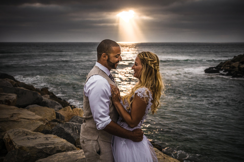 san diego wedding   photographer | married couple smiling and holding each other while smiling   with sunrays visible from afar