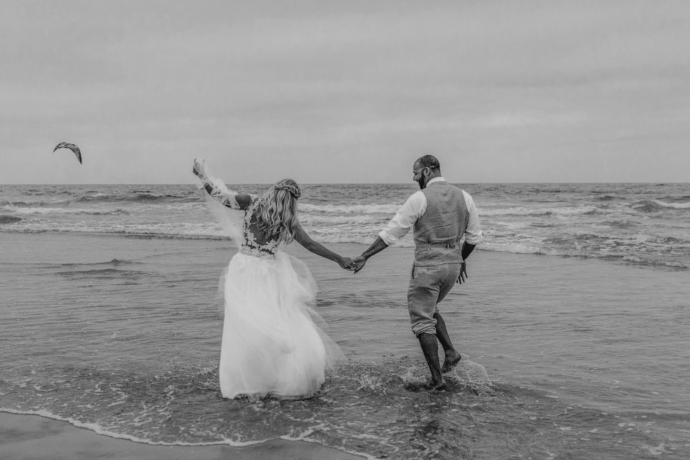 san diego wedding   photographer | black and white shot of couple holding hands while walking on   shore of beach