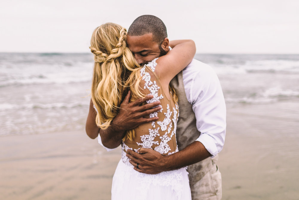 san diego wedding   photographer | married couple hugging each other smiling on beach shore