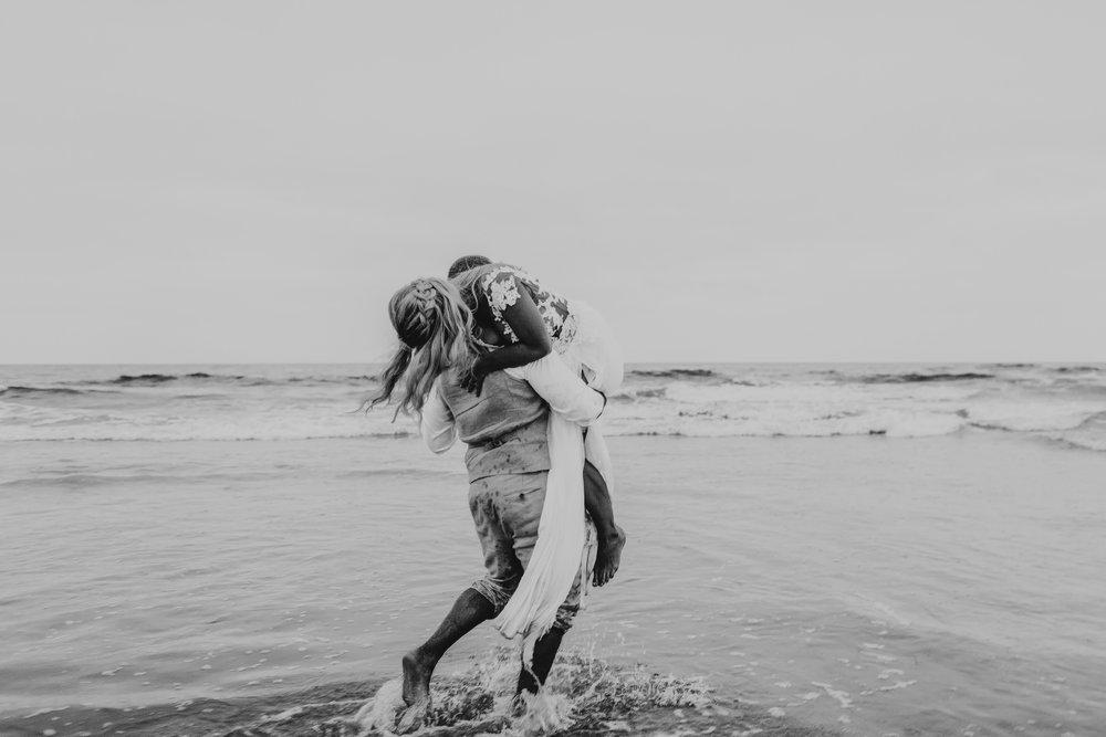 san diego wedding   photographer | married couple with groom carrying woman on his shoulder on   beach shore