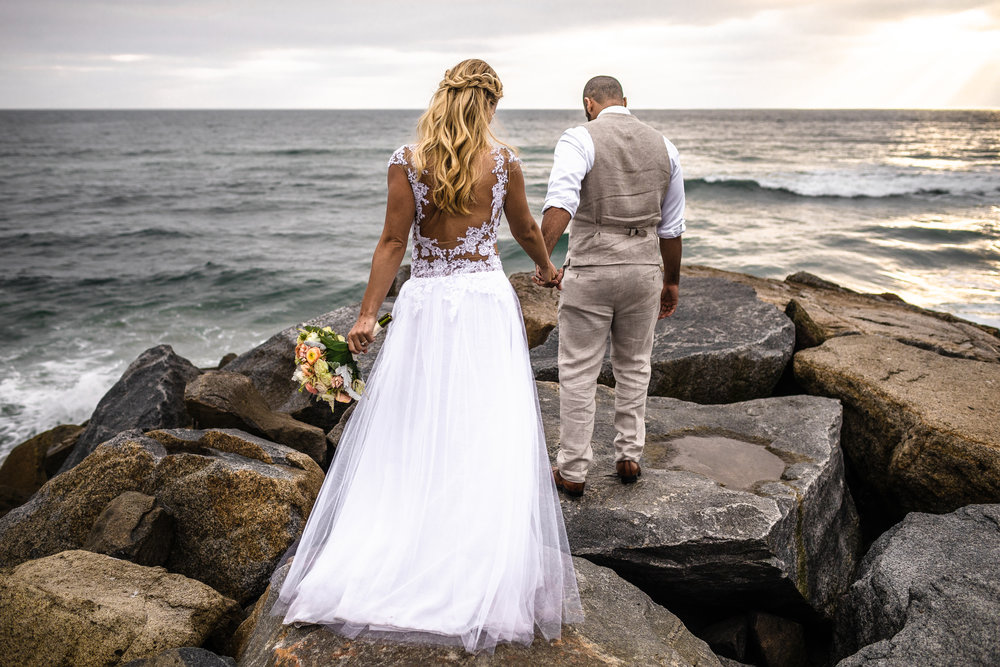 san diego wedding   photographer | groom leading bride's way on rocky shore with both of them   looking down