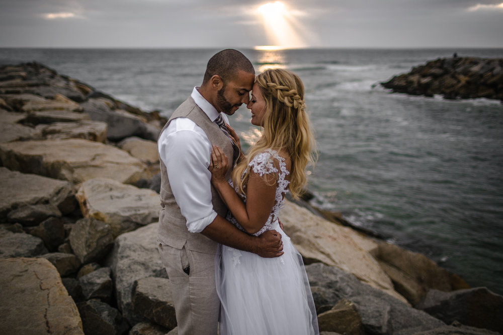 san diego wedding   photographer | couple holding each other while smiling at each other on rocky   shore with sunrays visible from afar in background