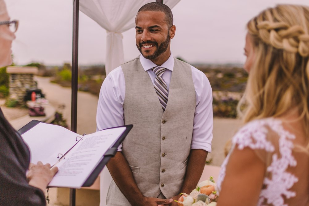 san diego wedding   photographer | groom facing the officiator while laughing with bride out of   focus