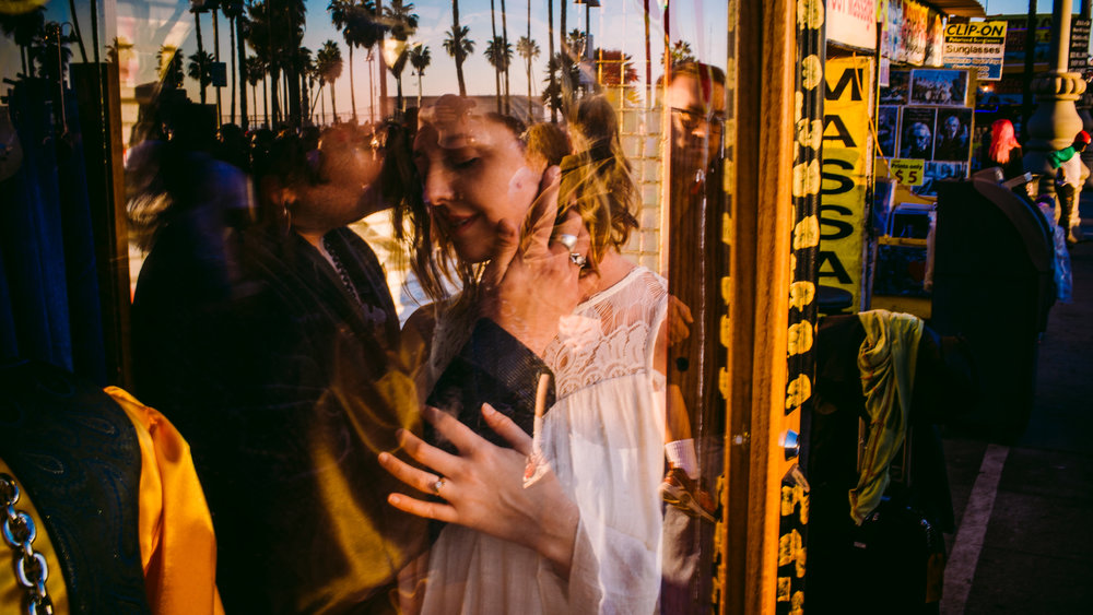 san diego wedding   photographer | couple behind glass of store glass window with palm trees   reflected on glass window