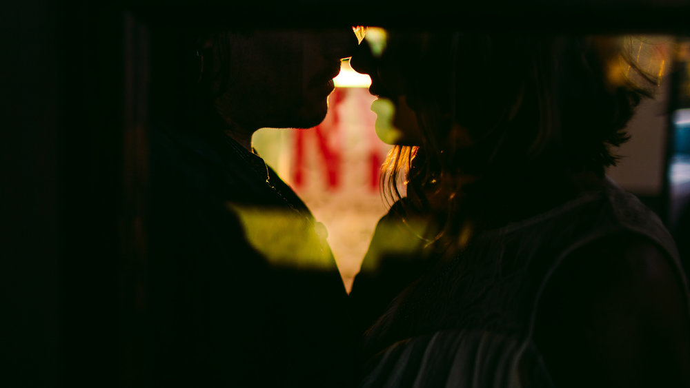 san diego wedding   photographer | low light picture of couple about to kiss as seen through   glass window