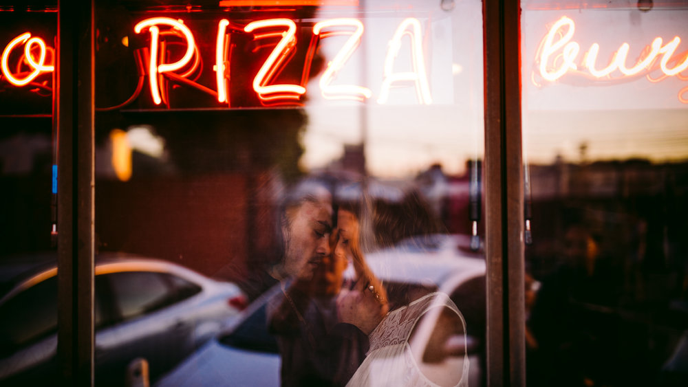 san diego wedding   photographer | couple about to kiss seen behind store glass window under neon   pizza sign