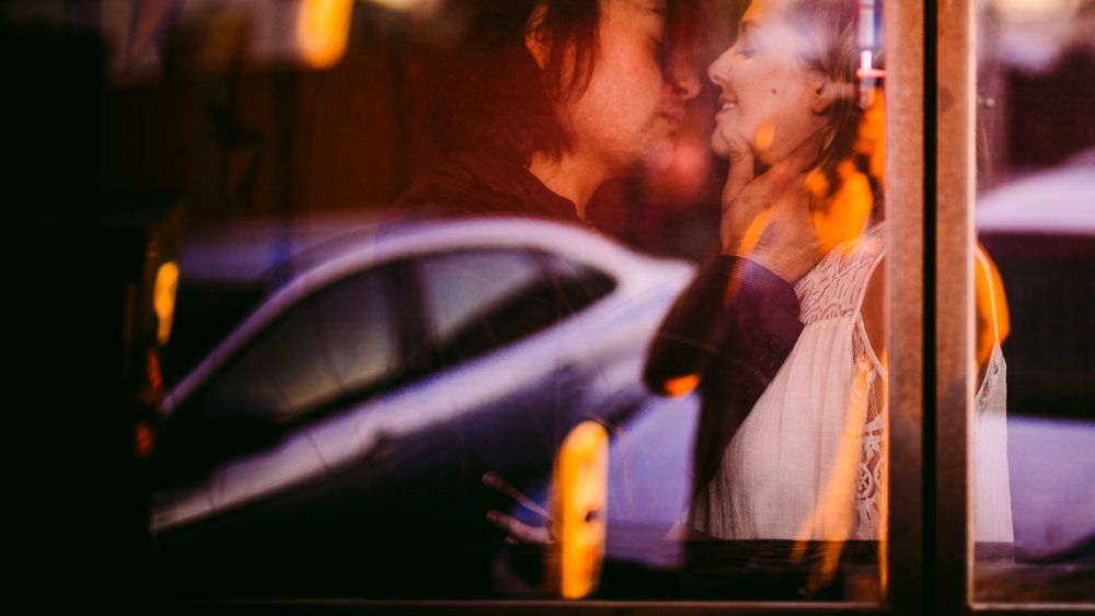 san diego wedding   photographer | man holding woman's face while woman smiles seen through store   glass window