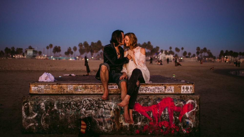 san diego wedding   photographer | couple sitting on concrete platform with man kissing woman's   nose