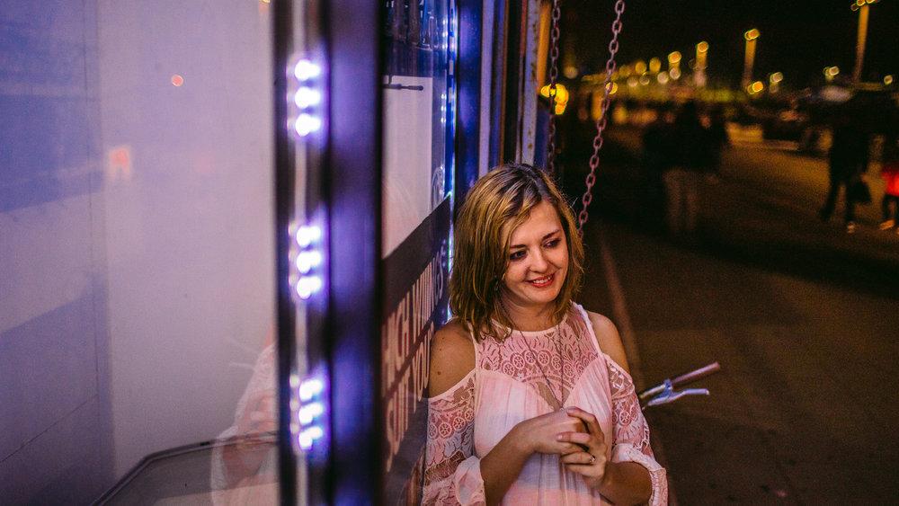 san diego wedding   photographer | woman in white dress smiling while leaning against store glass   window