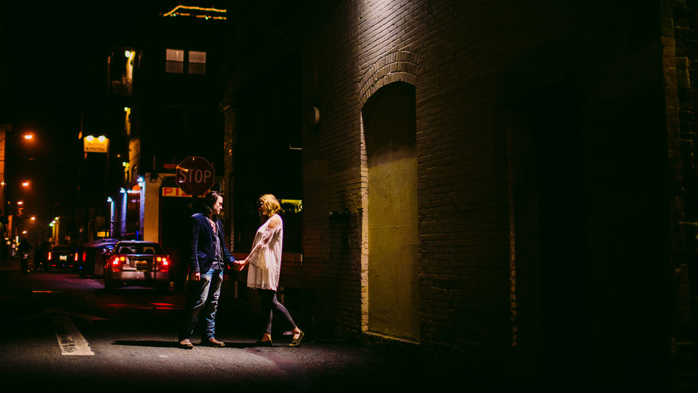 san diego wedding   photographer | woman walking toward man under streetlight in the night