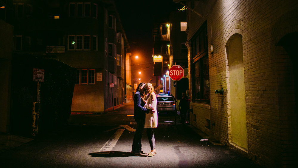 san diego wedding   photographer | couple kissing under streetlight at night with stop sign in   the background