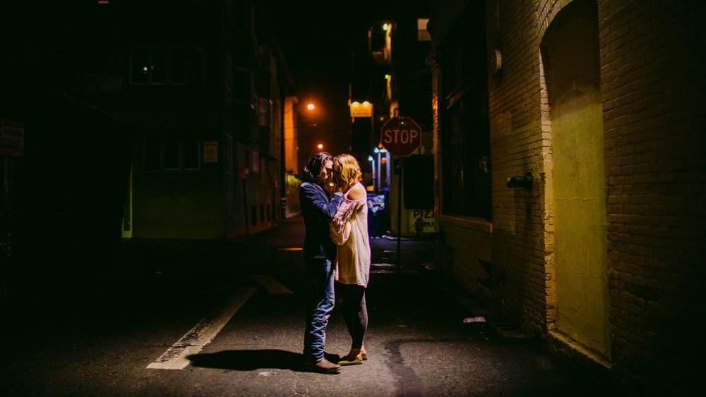 san diego wedding   photographer | couple about to kiss under streetlight at night with stop sign   in the background