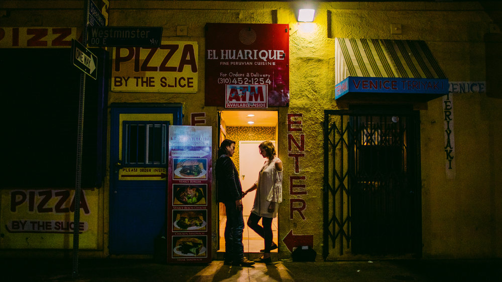 san diego wedding   photographer | man and woman looking at each other in doorway of yellow   building