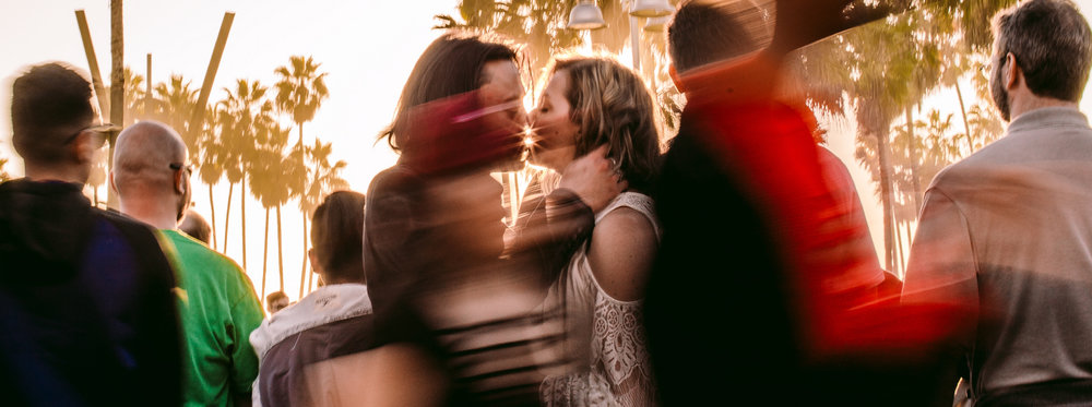 san diego wedding   photographer | long exposure shot of couple kissing in crowd with palm trees   in background