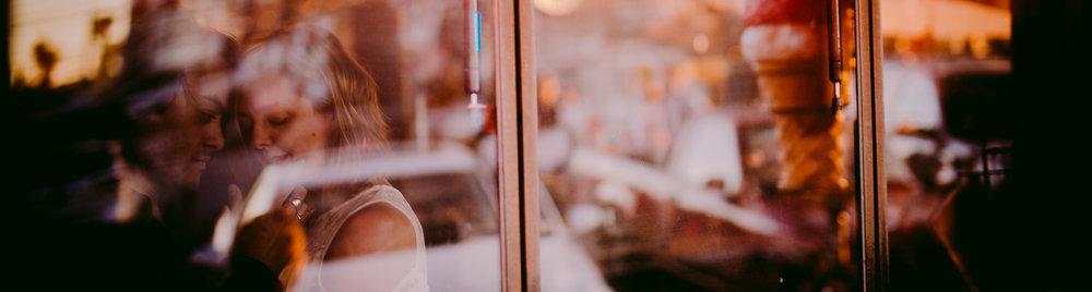 san diego wedding   photographer | man holding his hand against woman's face as seen through   glass window