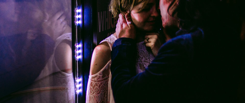 san diego wedding   photographer | man kissing woman with his hand on her neck while woman leans   on window with led light