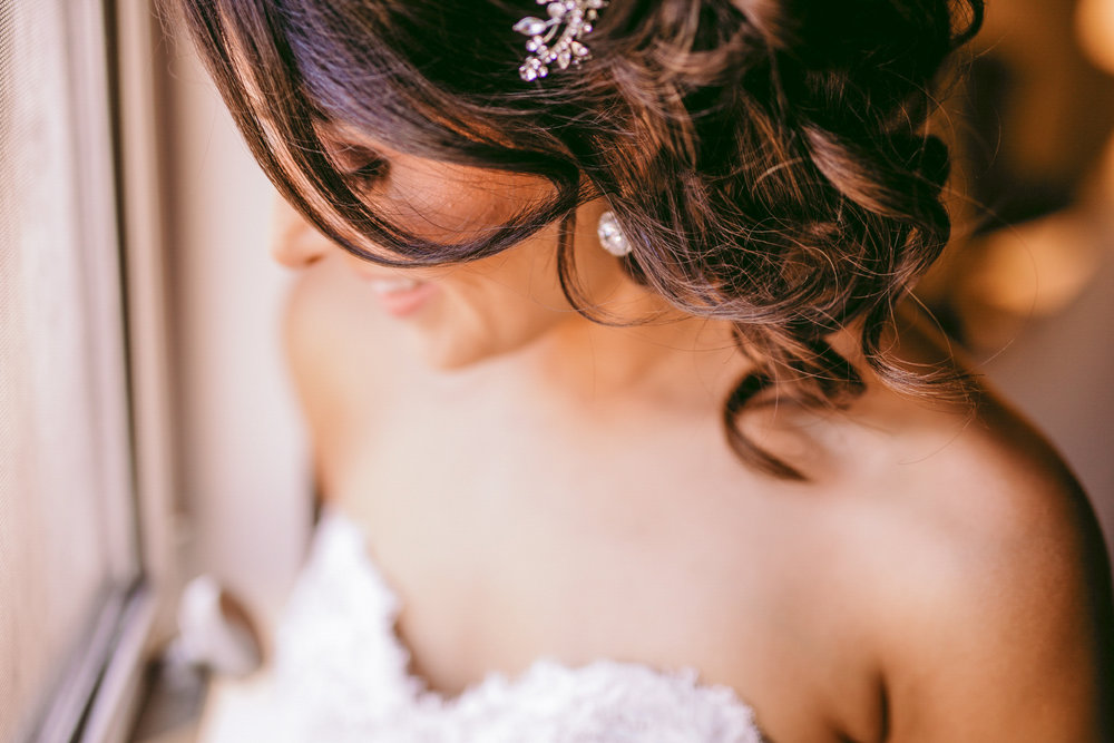 san diego wedding   photographer | woman with earrings wearing wedding dress looking down to her   side by the window