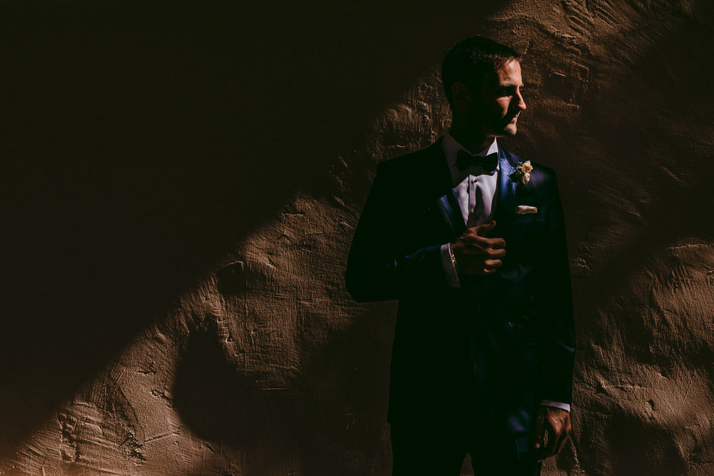 san diego wedding   photographer | man in blue suit leaning against wall looking to his right