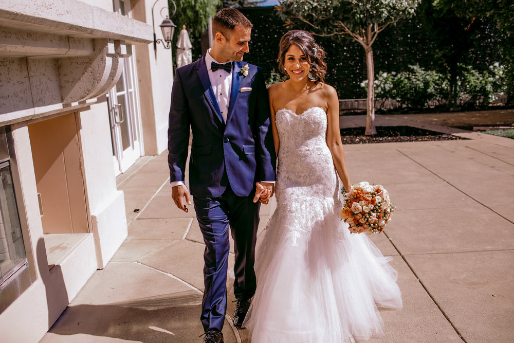 san diego wedding   photographer | couple walking while holding hands while man looks to woman   holding bouquet of flowers