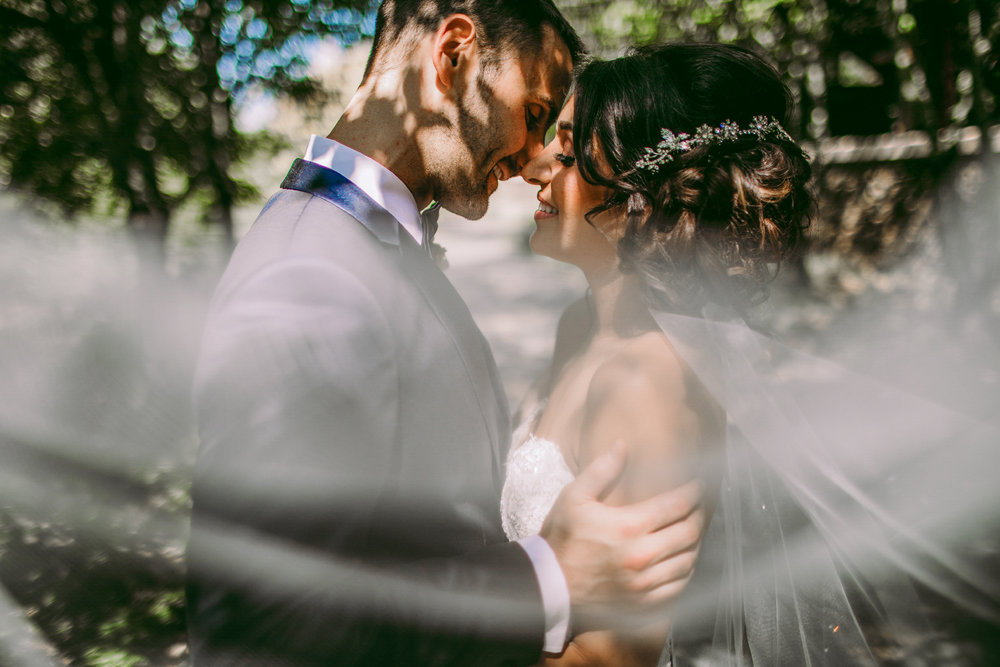 san diego wedding   photographer | couple about to kiss while man holds woman's shoulder seen   through veil