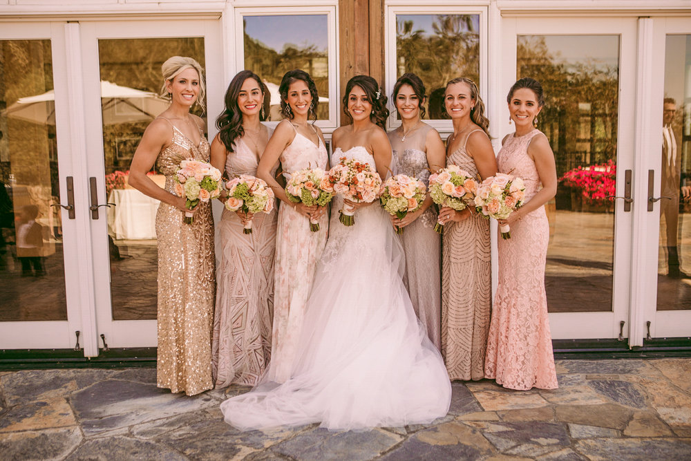 san diego wedding   photographer | women in dresses holding bouquets of flowers standing in front   of building with glass windows