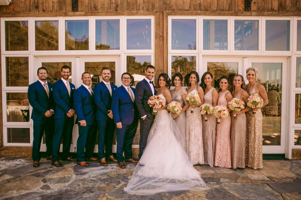 san diego wedding   photographer | group of men in blue suits and women in dresses standing in   front of building with glass windows